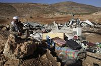 Palestinian man by remains of his house destroyed in Aqraba village West Bank